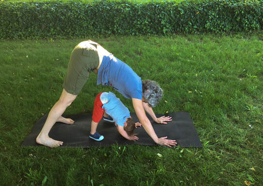 Grandma and grandson in downward facing dog